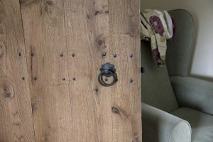 An image of a matte black ring turn handle set fixed onto a wooden door.
