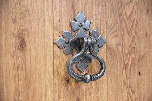 An image of a shakespeare door knocker with a pewter finish, fixed onto a door.