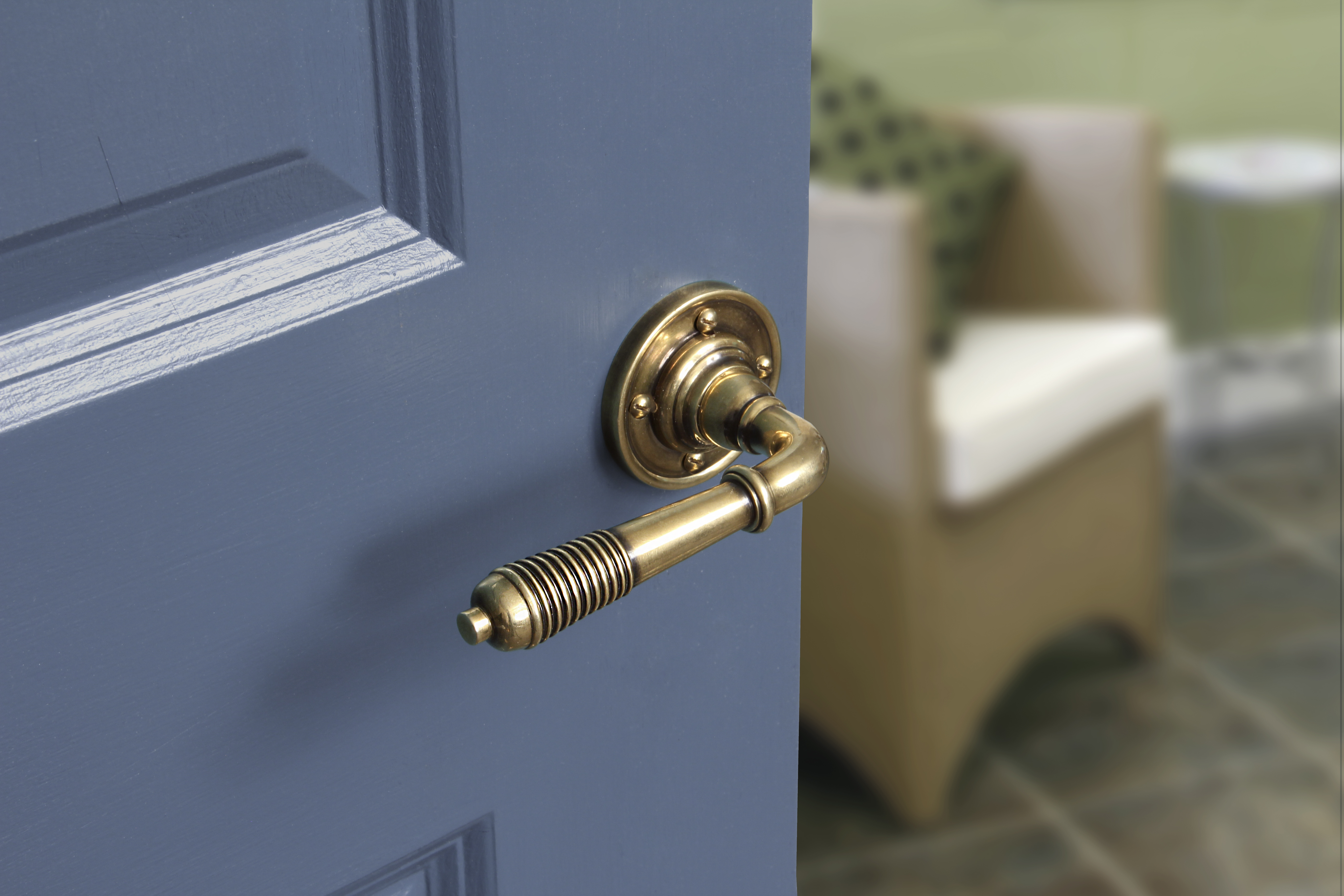 An image of a cylinder brass door handle, fitted onto a navy blue door.