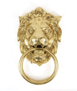 An image of a lion's head door knocker with a gold finish.