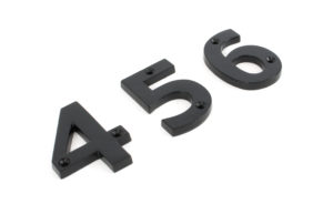 An image of front door numbers with a black finish, sold by Heart of Wood.