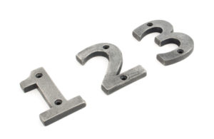 An image front door numerals, made from iron and finished in a matte silver colour.