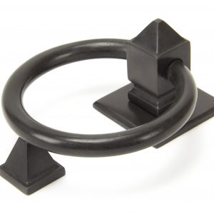 An image of a black, ring shaped door knocker sold by Heart of Wood.